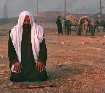A man offers a prayer at the street